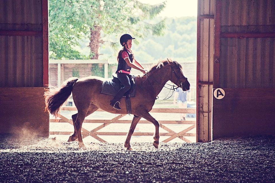 Girl riding pony backlit by sun
