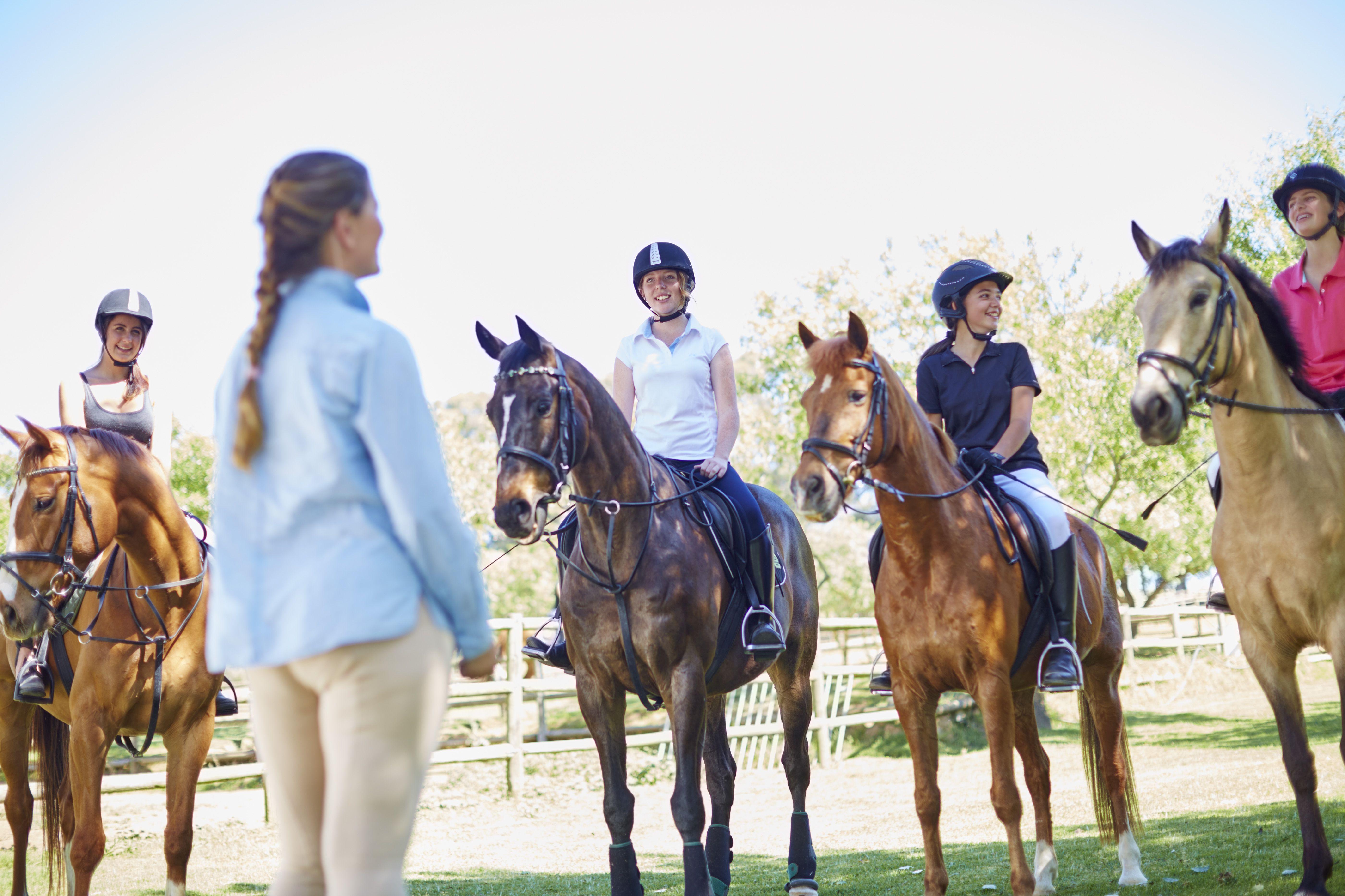 Entrenador y chicas a caballo en el anillo de equitación.