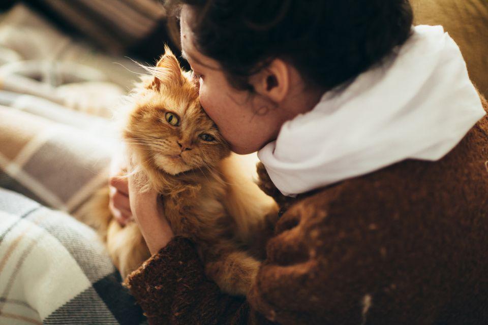 Mujer besando la cabeza del gato