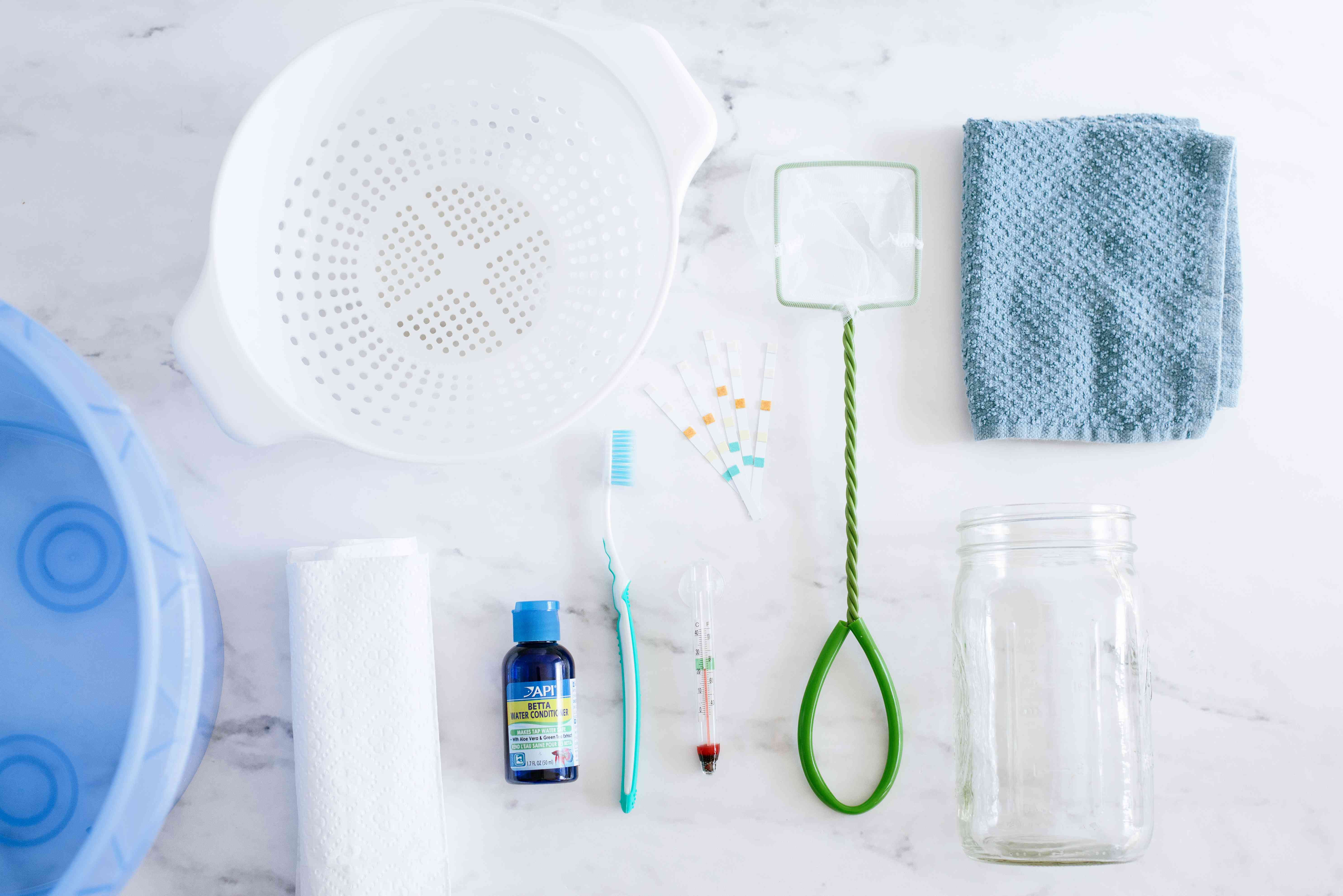 Materials to clean a fishbowl on white marbled surface