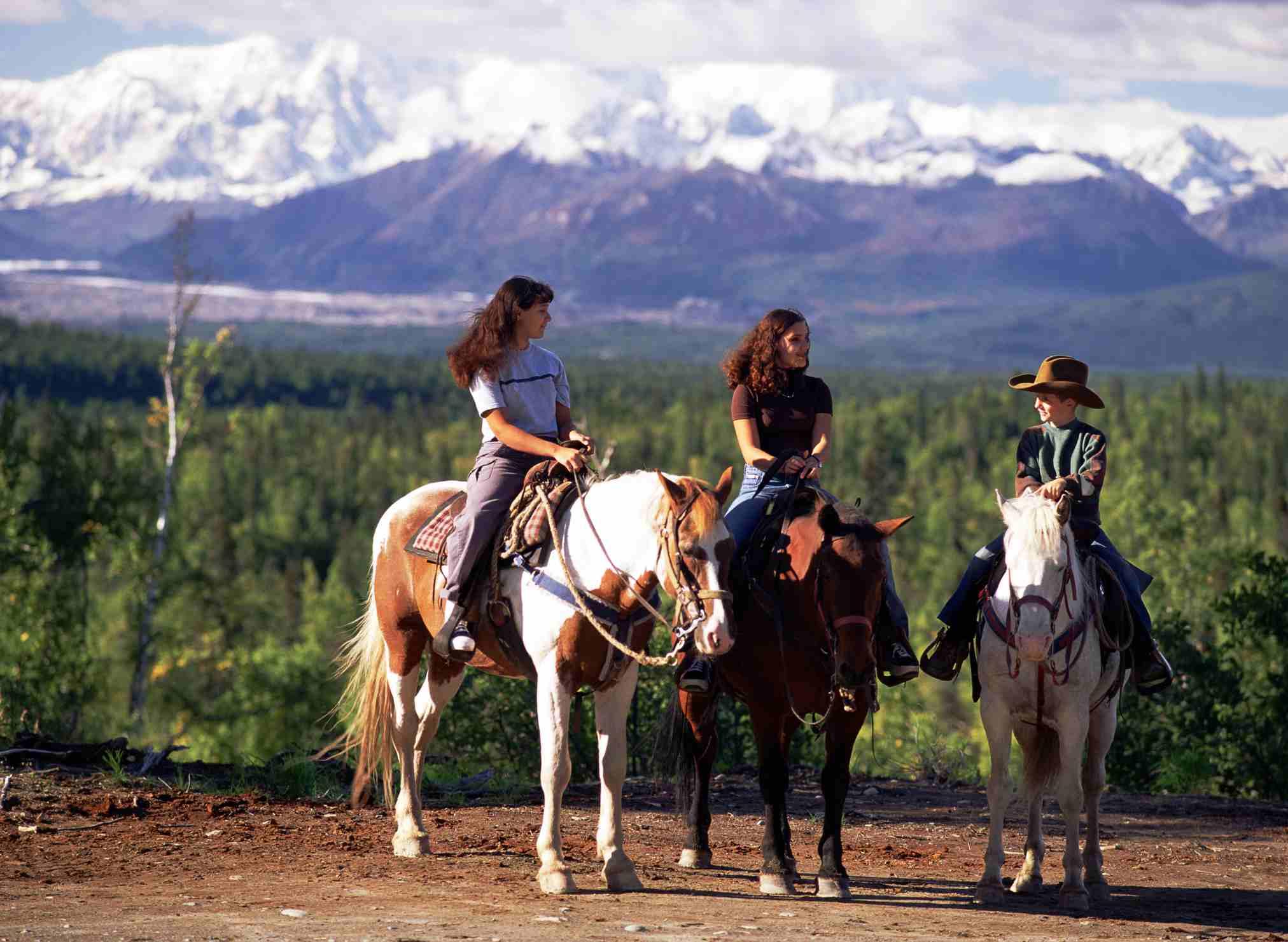 Tres personas sentadas en sus caballos