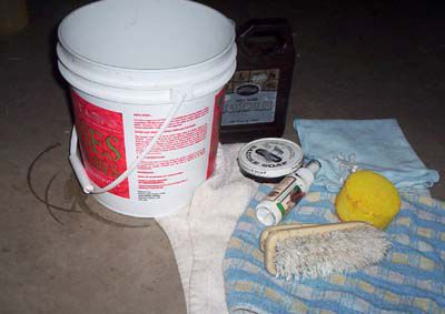 Equipment for cleaning a saddle, including a brush, sponge, bucket, and rags.