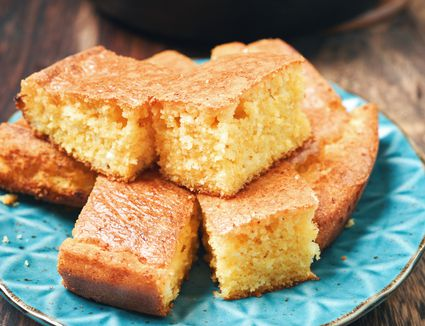 Pieces of cornbread on a blue plate.