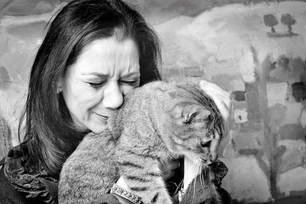 Photo of a sad woman holding a cat