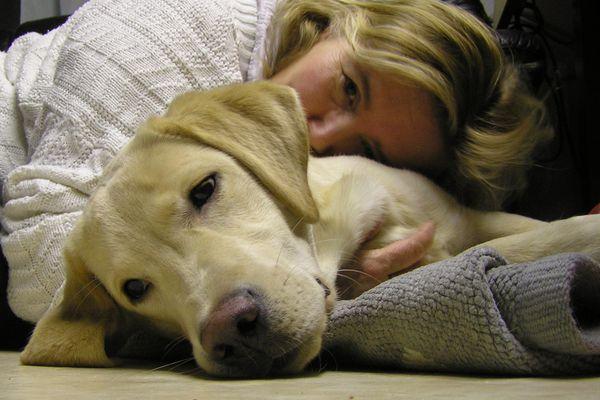 A woman cuddling with a dog