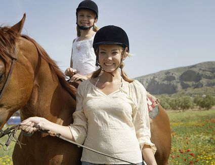 woman holding horse with child riding