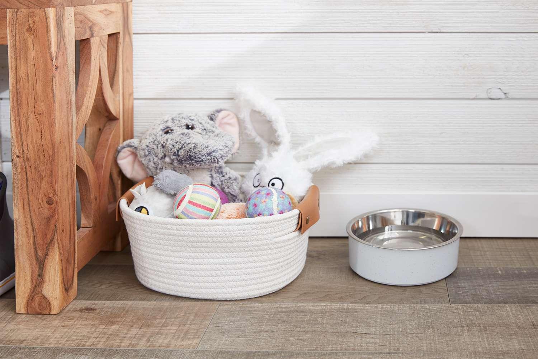 juguetes para mascotas en una canasta con un tazón de agua