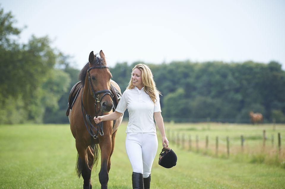 Jinete femenino caminando caballo en el paddock.