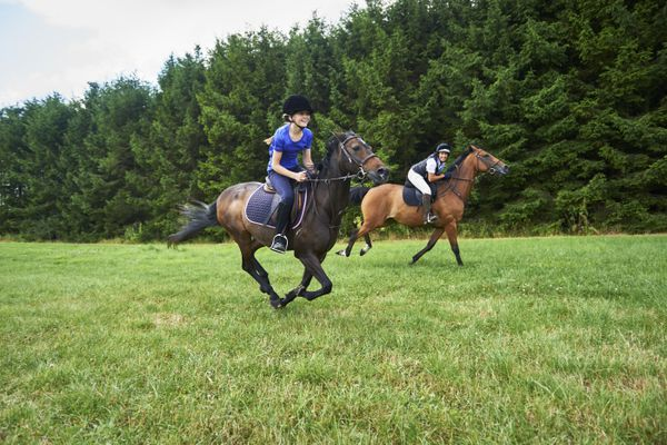 Side view of girl and mature woman wearing riding hats galloping on horseback