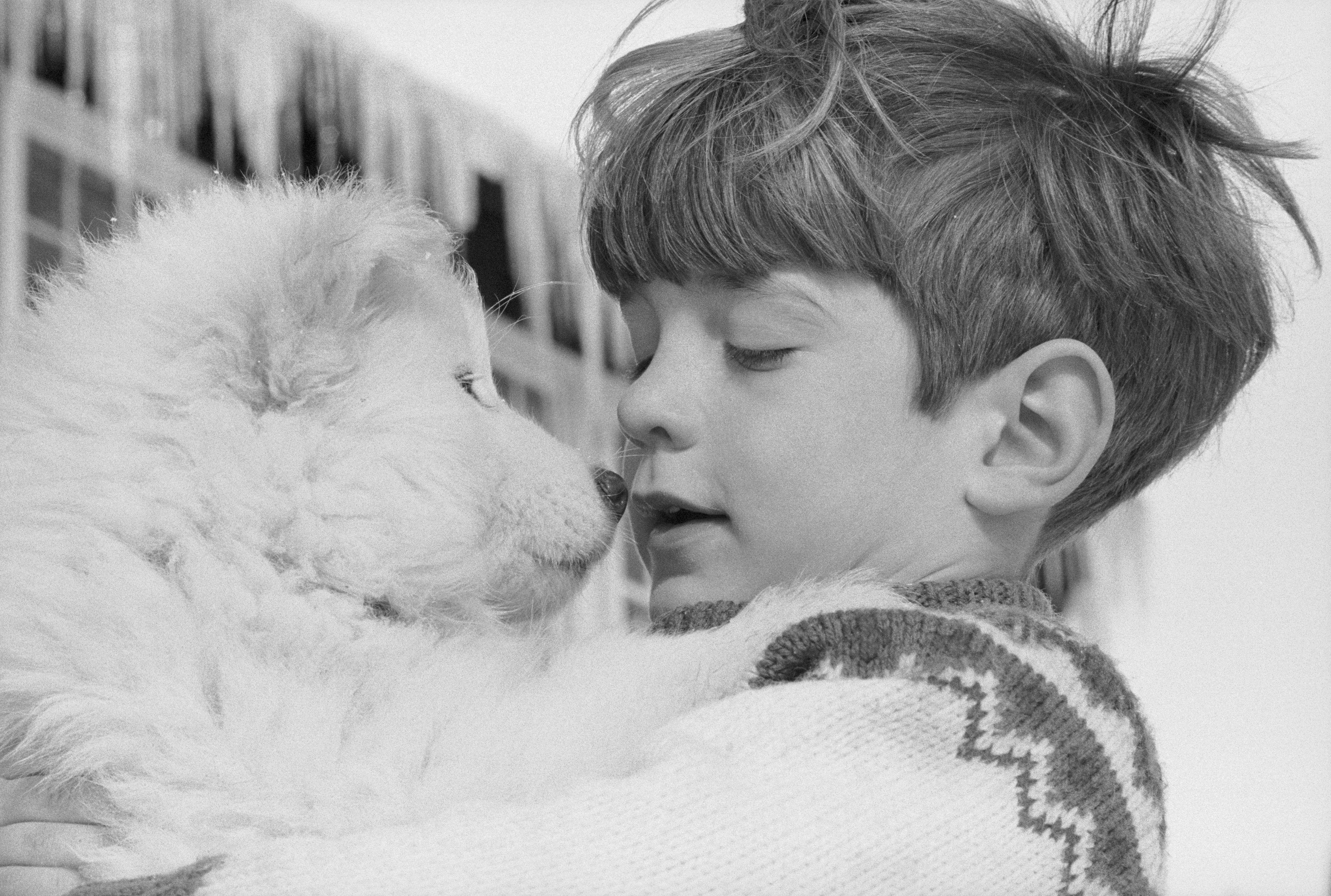 John F. Kenney Jr. sosteniendo cachorro samoyedo