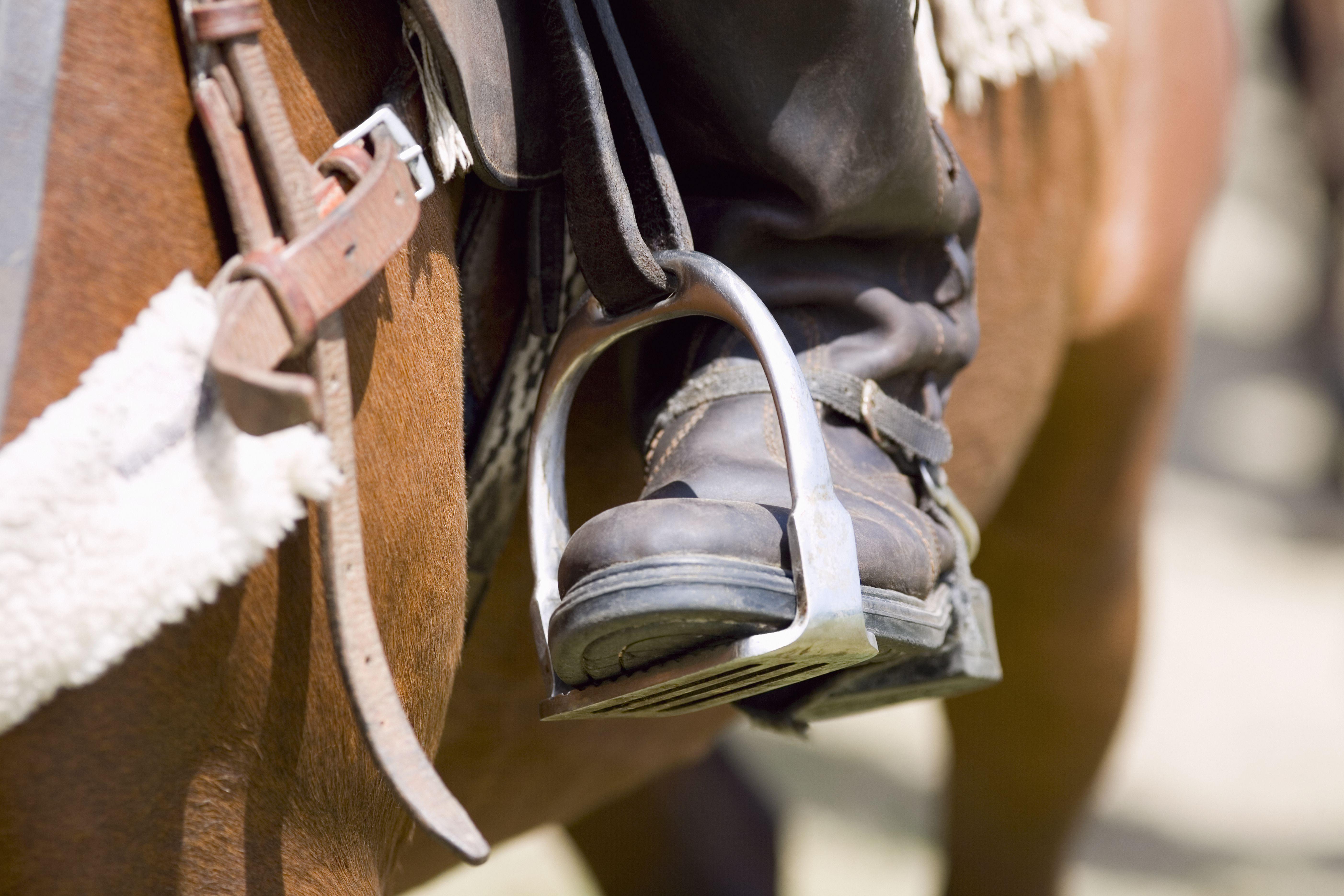 Close-up of a person's leg in a stirrup