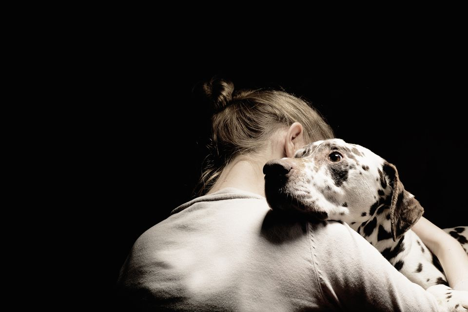 girl embracing her dog, studio shot