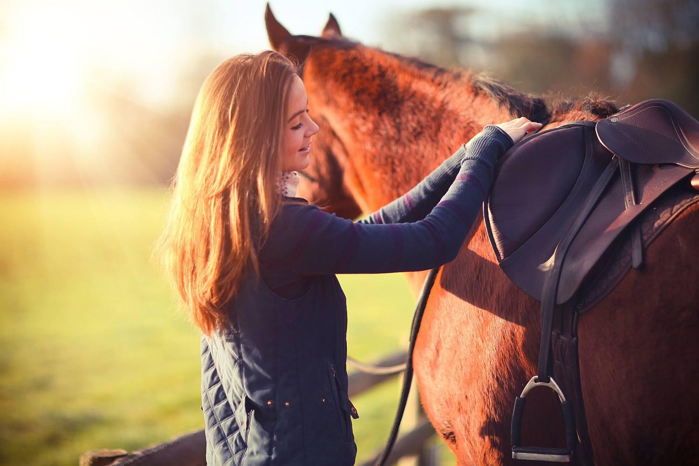 Woman checking horse's saddle.