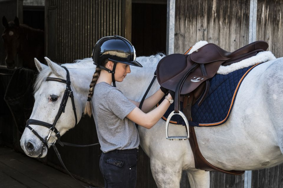 Teenage girl horse rider with a grey horse outside a stable, adjusting the girth and saddle.