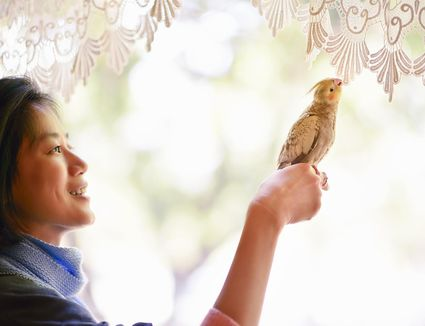 Cheerful woman and pet bird perched on her finger