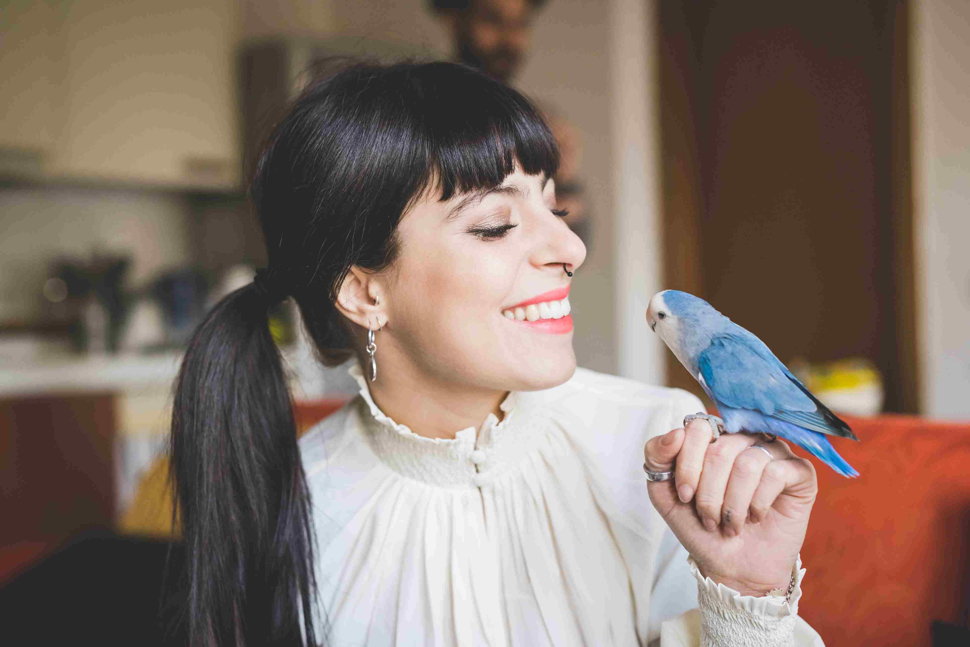 Mujer joven sonriendo al pájaro mascota en el interior