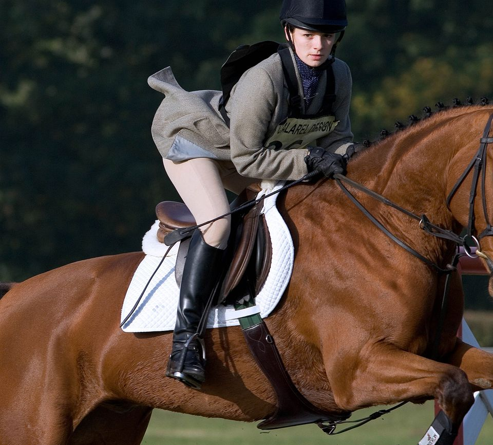 Girl in English riding clothes, riding a horse as it jumps an obstacle