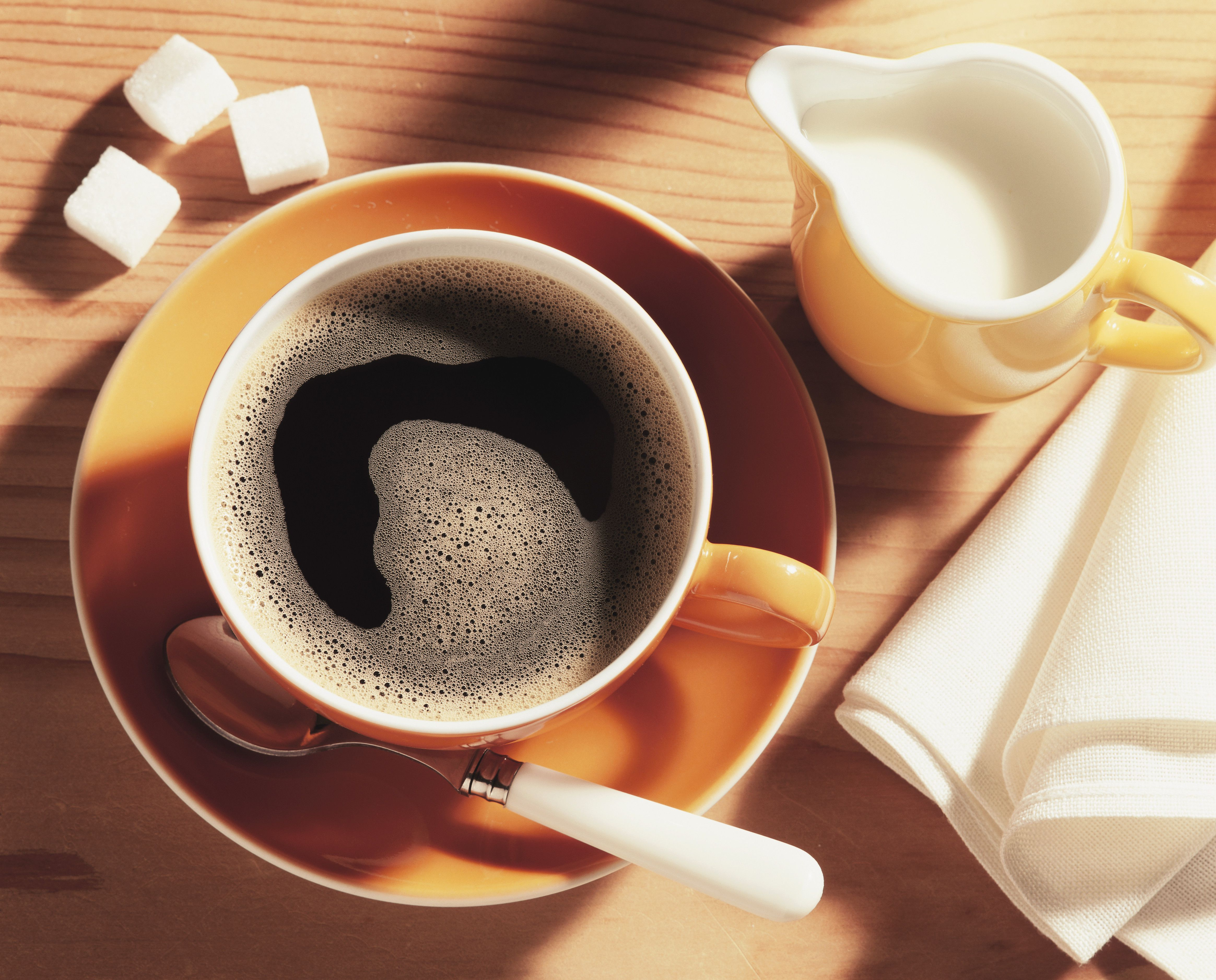 A cup of coffee and a jug of coffee cream