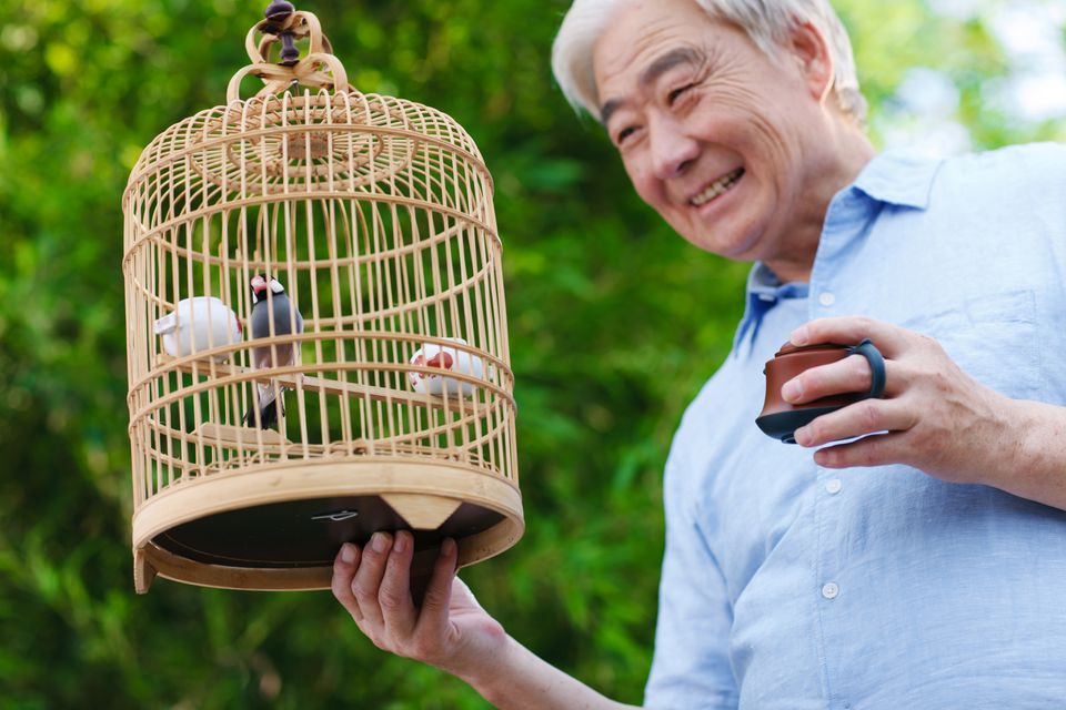 man holding bird cage with pet bird
