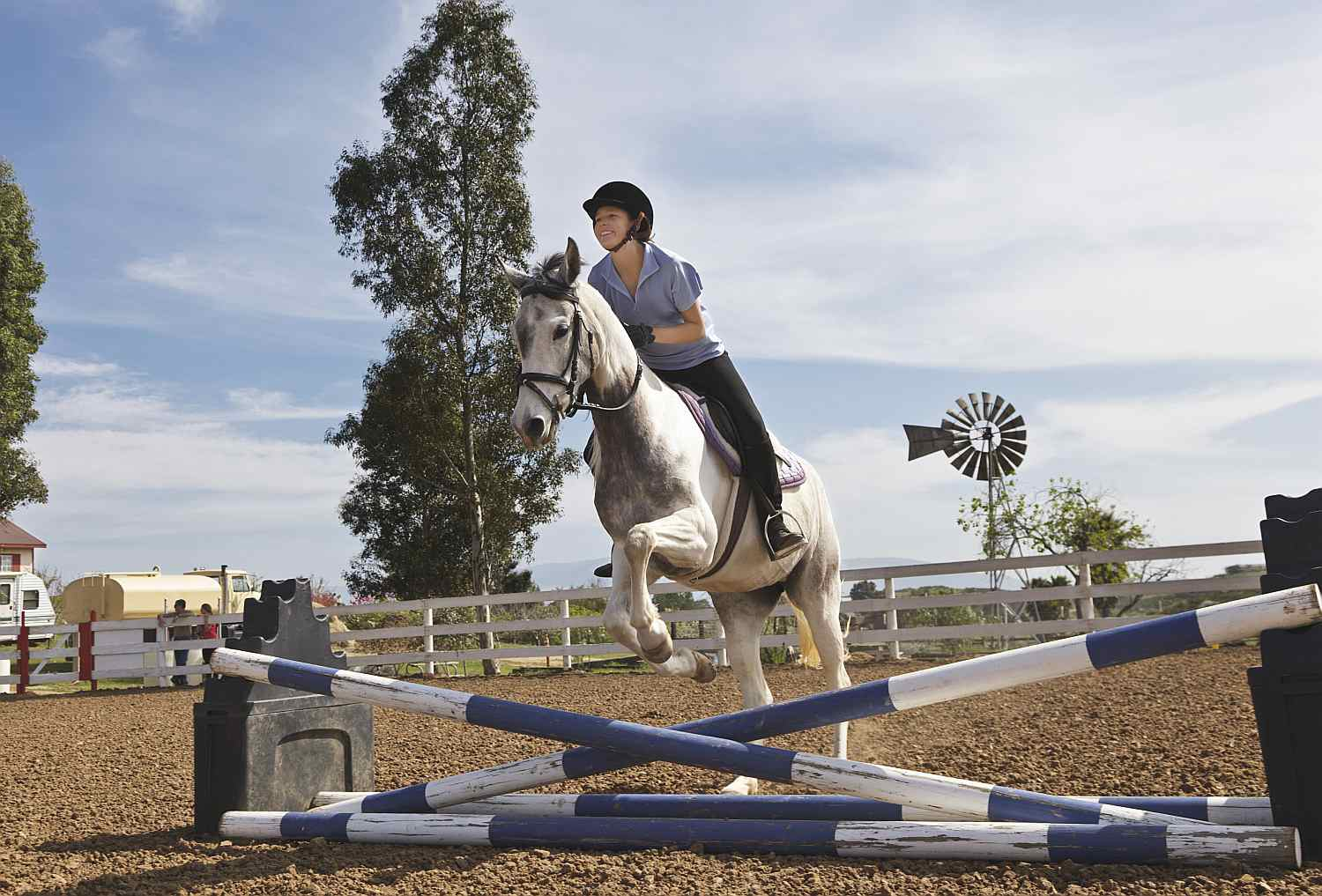 Girl jumping her horse over cross rails