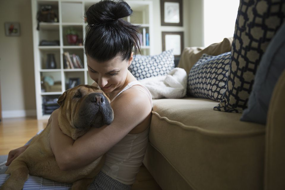 Woman hugging dog on living room floor