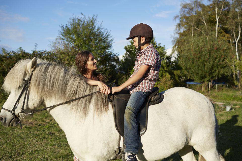 Madre ayudando a hijo con equitación