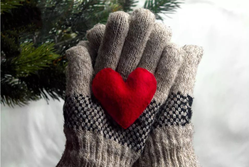 Two gray gloves holding a felt red heart.