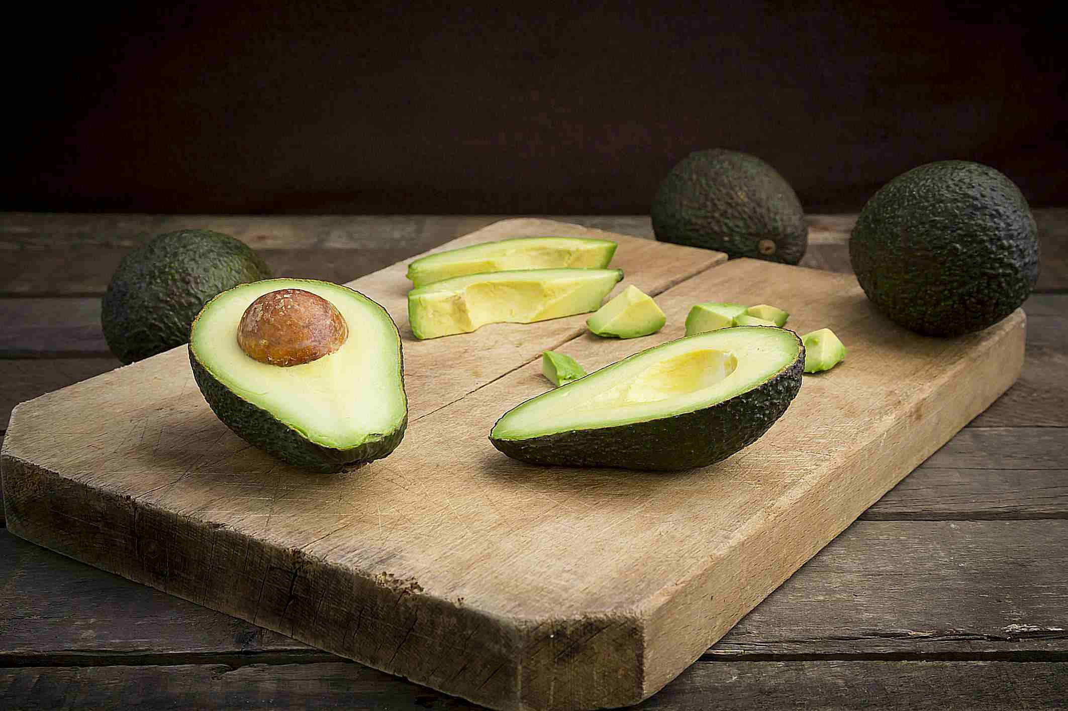 Full and cut up avocados on cutting board