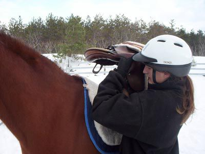 Woman putting saddle on a horse