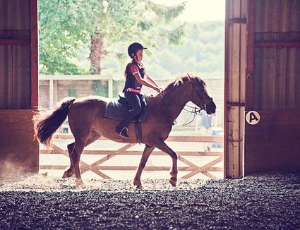 Girl riding a horse in a stable.