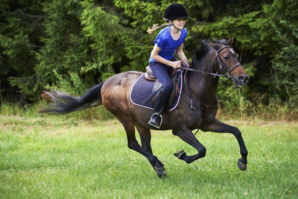 Side view of girl wearing riding hat galloping on horseback