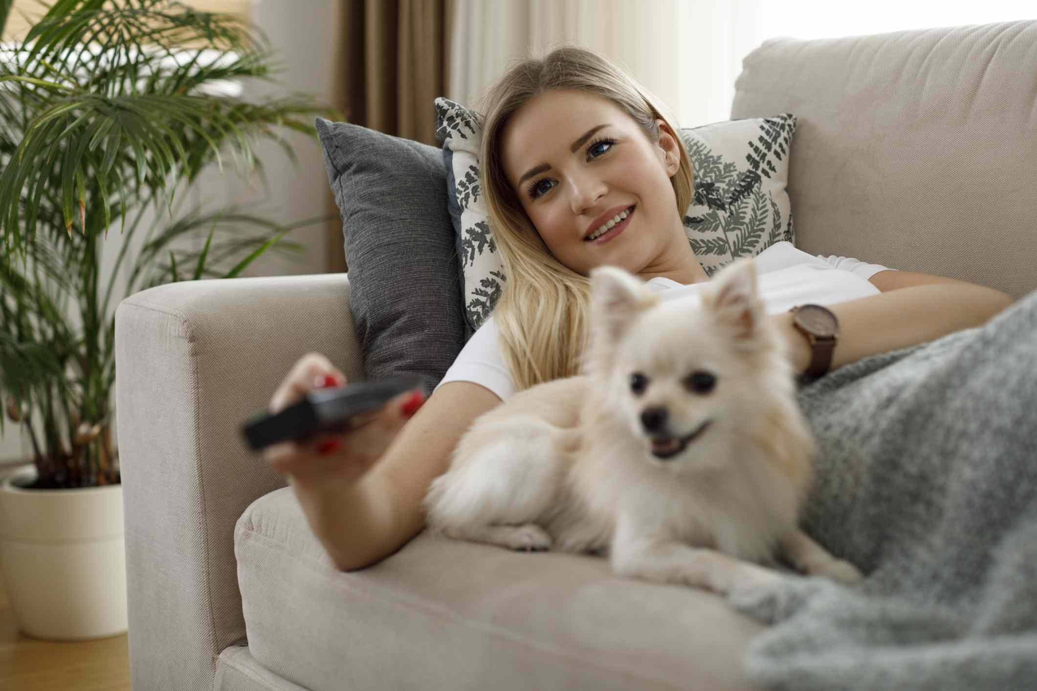 woman watching tv with her dog