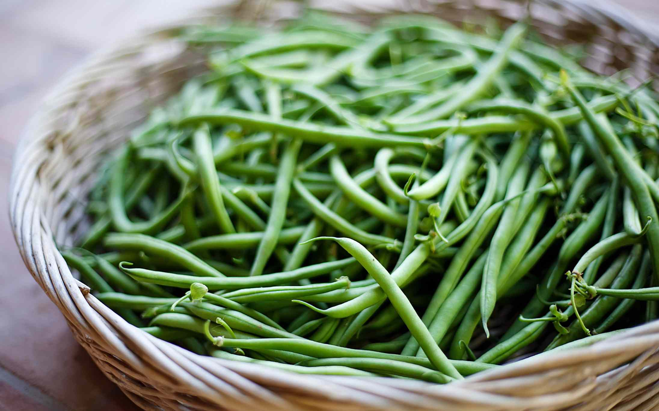 Woven basket full of green beans on table.