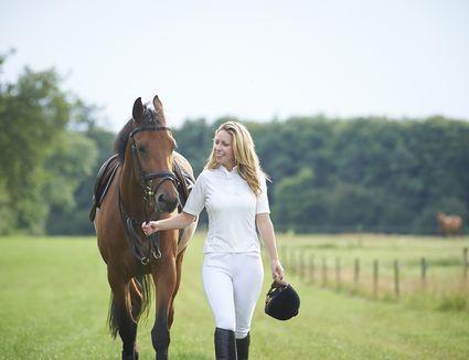 Female jockey walking horse in paddock.