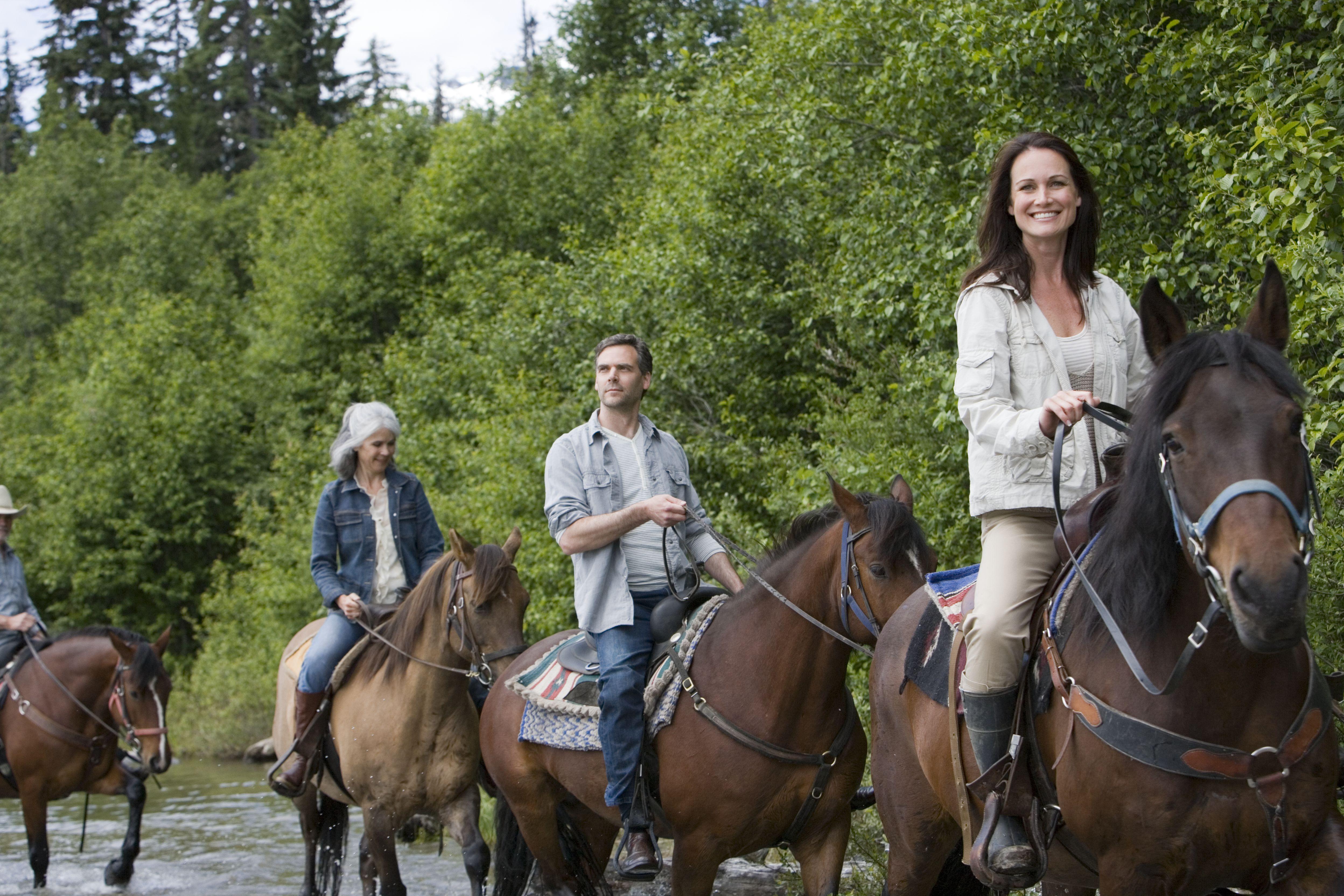 Grupo de cuatro jinetes cruzando el río, mujer mirando a cámara