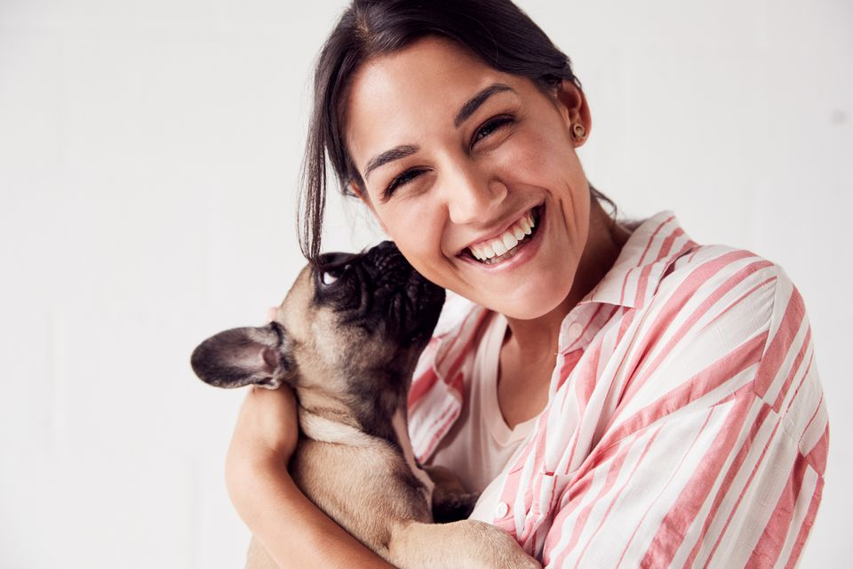 Studio Portrait of Smiling Young Woman Holding an Affectionate French Bulldog Puppy