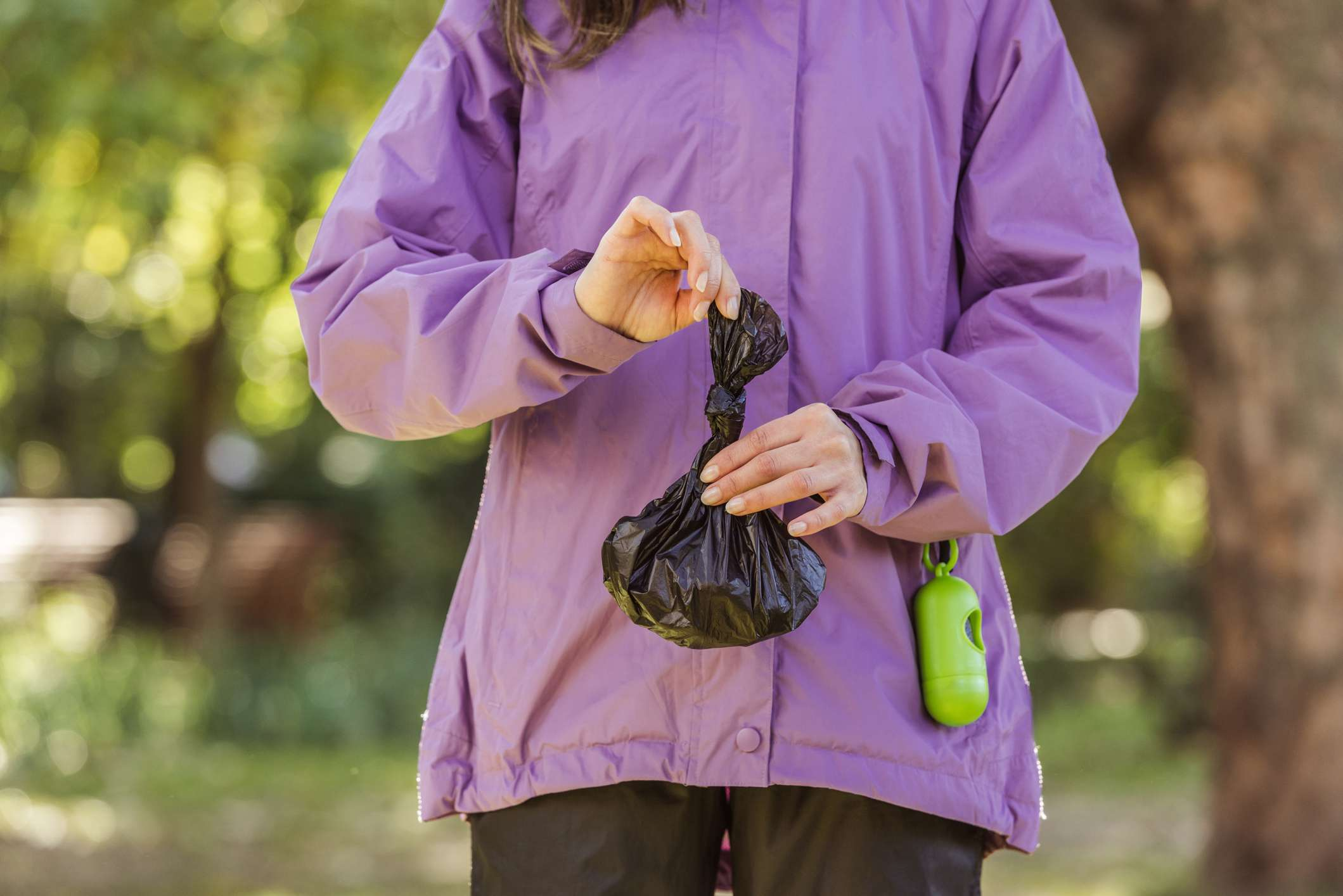 Neck down shot of woman in purple jacket with doggie poop bag and holder.