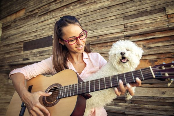 young woman playing guitar with dog