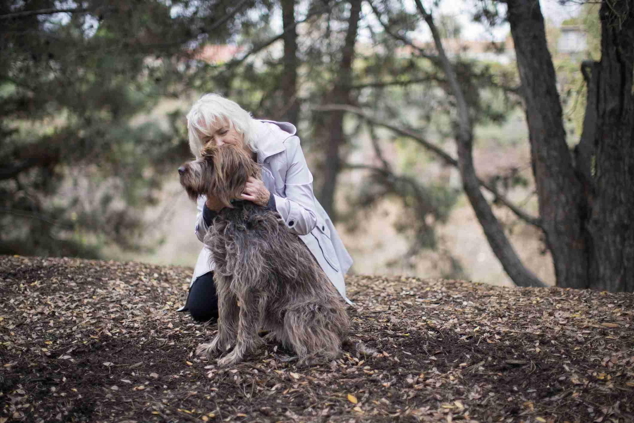 Senior woman hugging her dog outdoors