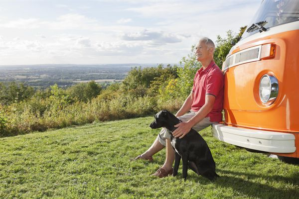 Senior man sitting on a bumper of a camper van with his dog.