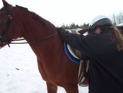 Chica preparándose para montar un caballo.