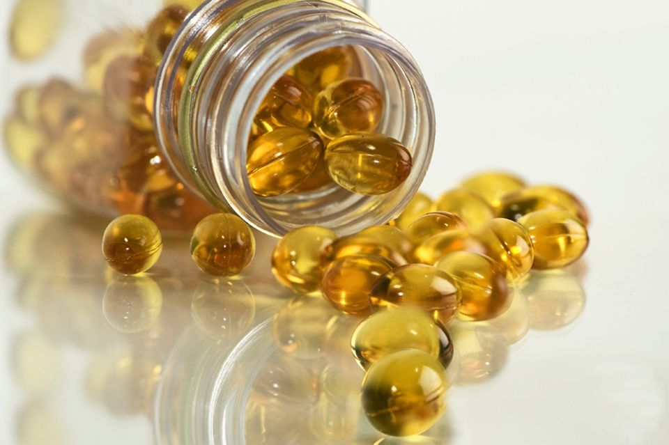 Fish oil soft gel capsules spilling out of a clear bottle.