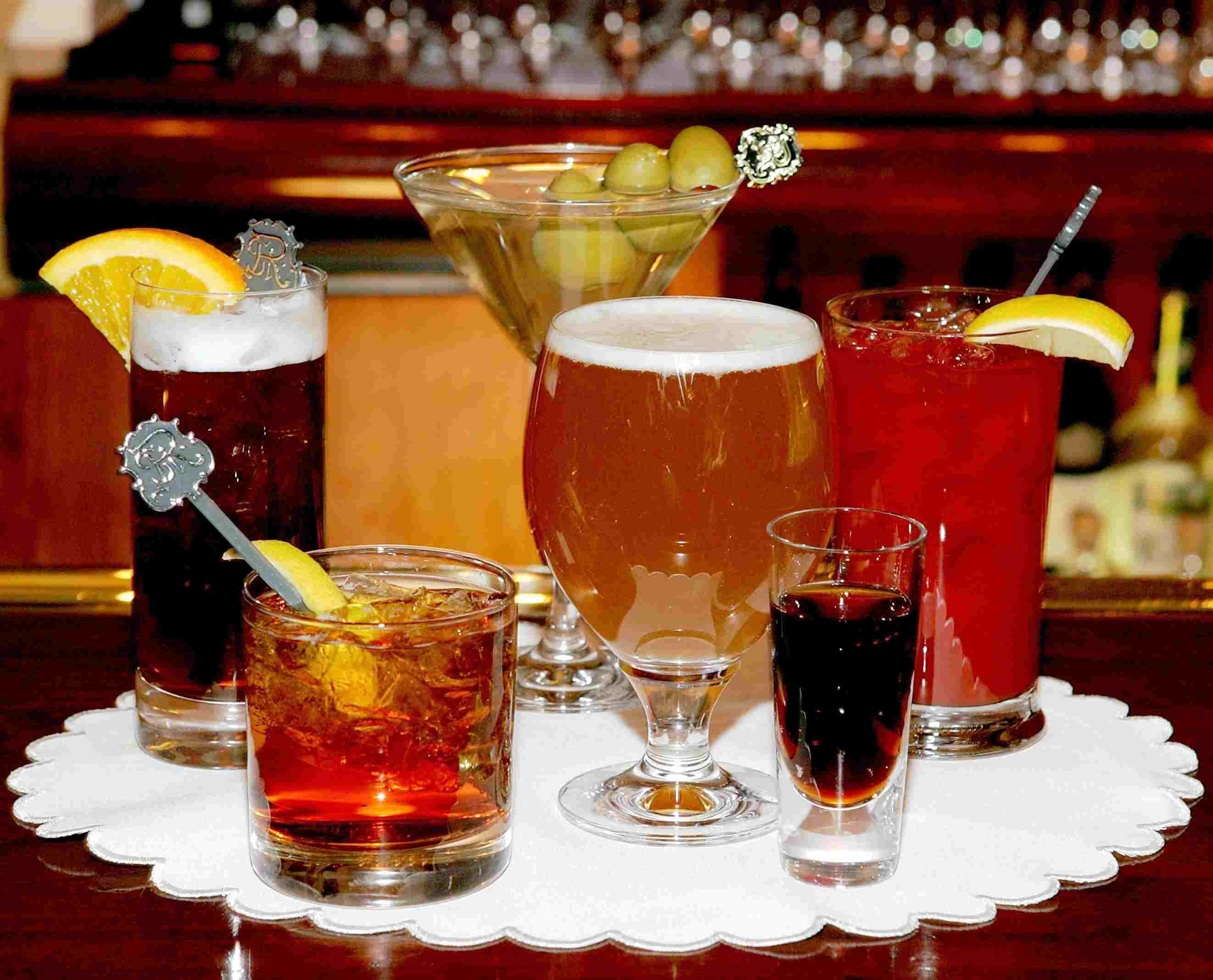 A variety of alcoholic drinks on a table, including beer, shots, and hard liquor., also toxic to dogs