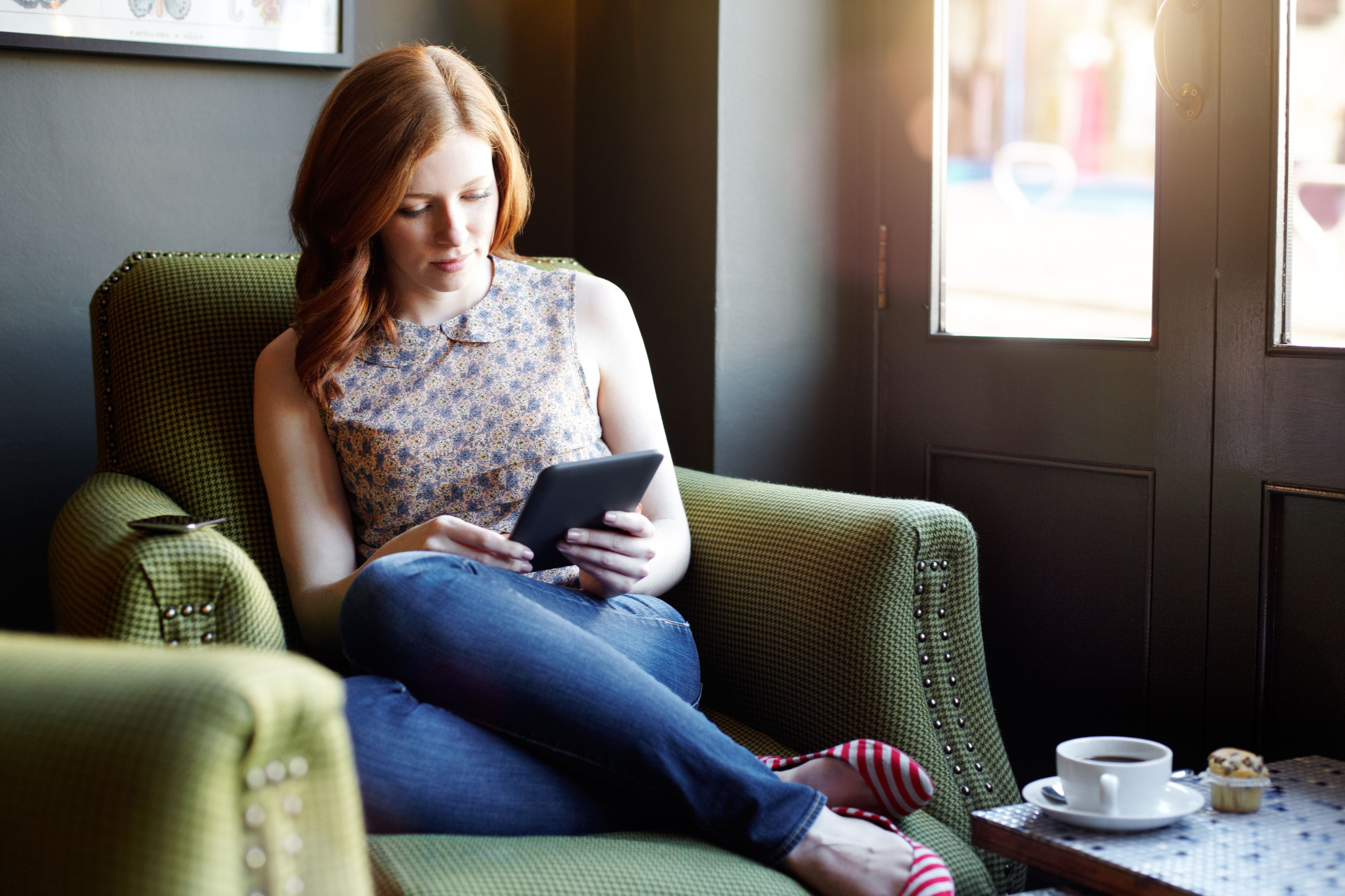 Woman reading ebook on tablet in coffee shop