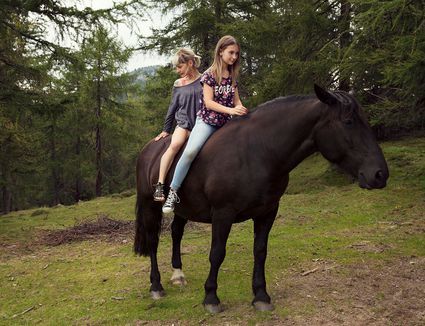 Girl and woman sitting bareback on horse in a forest.