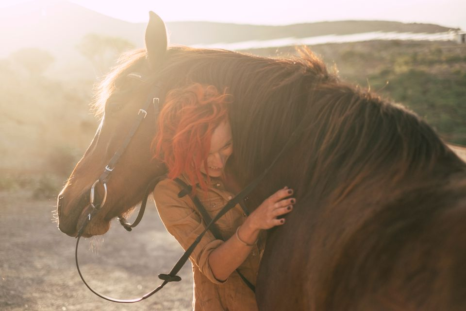 Woman Embracing Horse On Field