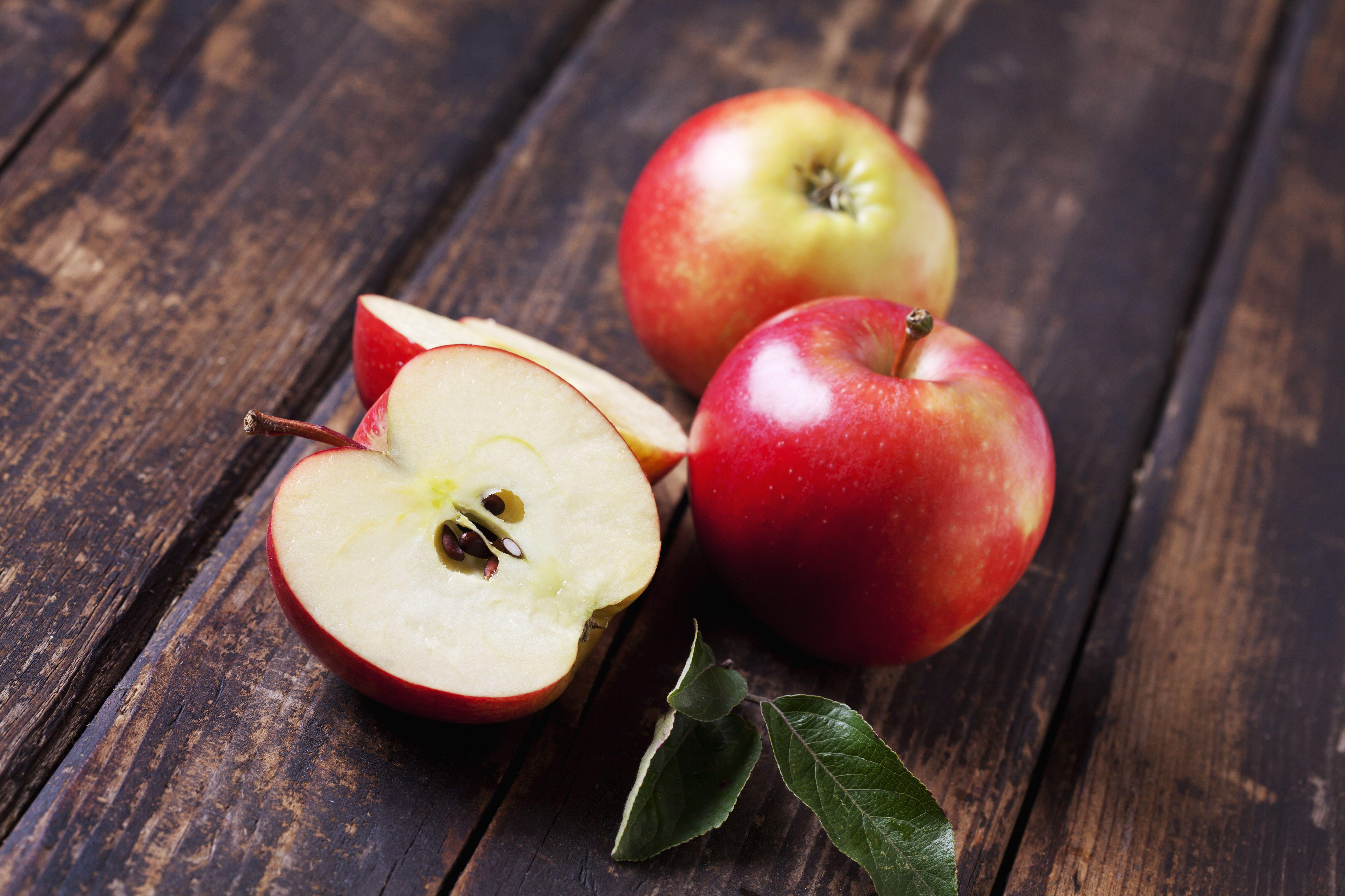 Manzanas rojas enteras y en rodajas en madera oscura
